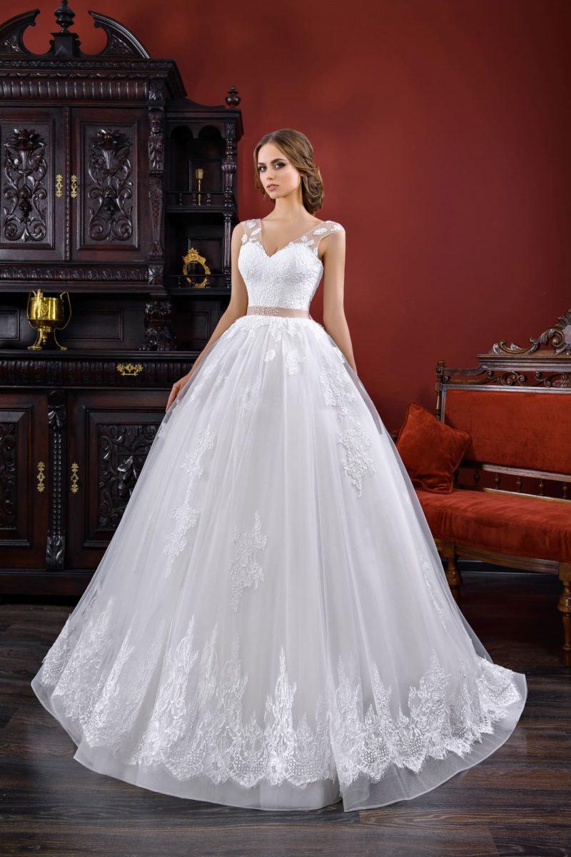 Пышное свадебное платье с полупрозрачными бретелями и розовым поясом на талии.