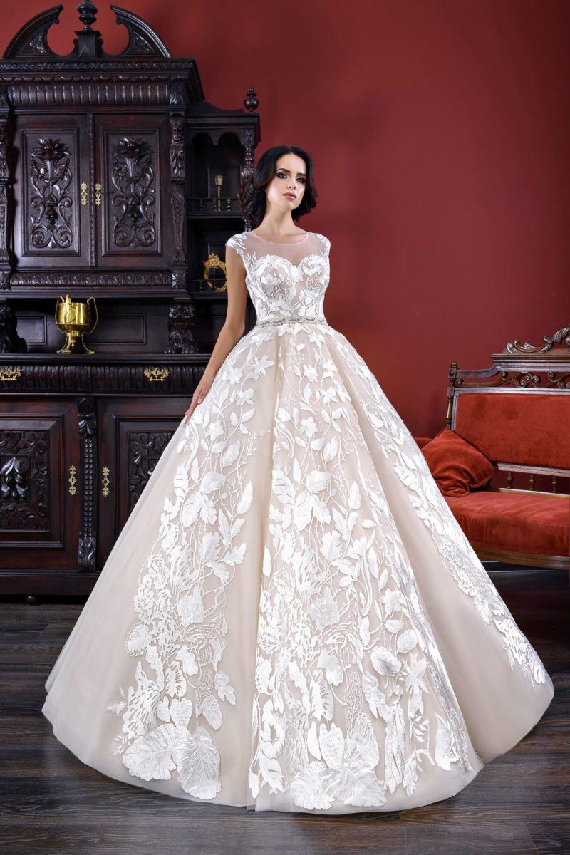 Бежевое свадебное платье пышного силуэта с закрытым верхом и крупной отделкой.