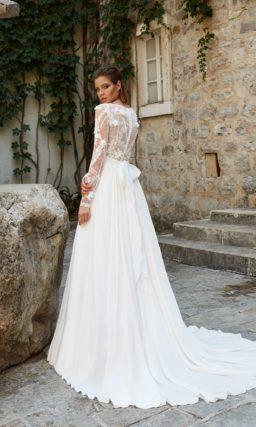 Свадебное платье с белой шифоновой юбкой А-силуэта и полупрозрачным верхом.