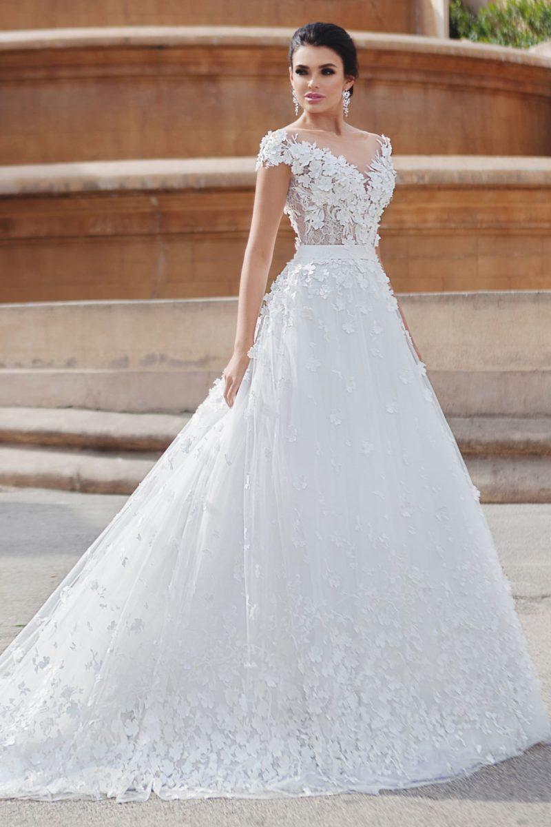 Эффектное свадебное платье А-силуэта с объемной отделкой и коротким рукавом.
