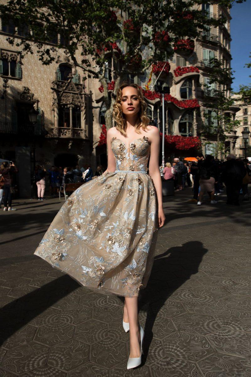 Вечернее платье бежевого цвета с открытым лифом, юбкой миди и аппликациями.