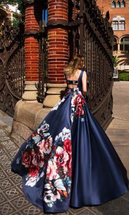 Вечернее платье из синей атласной ткани с принтом по подолу и округлым декольте.