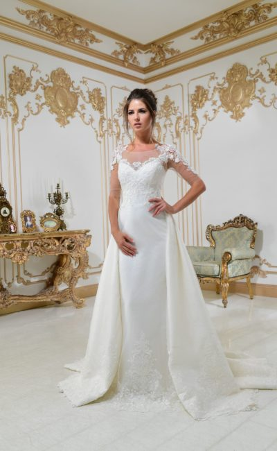 Свадебное платье А-силуэта с юбкой необычного кроя и длинным прозрачным рукавом.