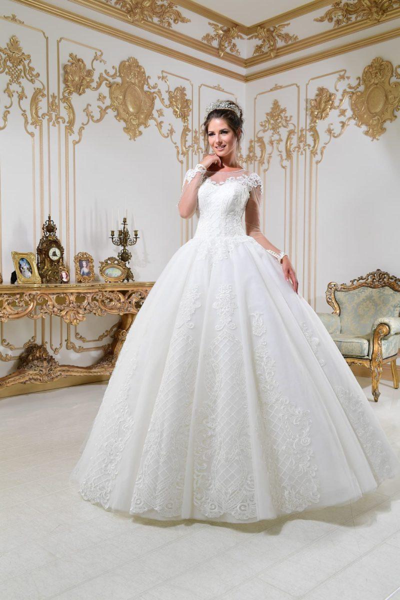 Свадебное платье с подчеркнуто пышным силуэтом и длинным прозрачным рукавом.