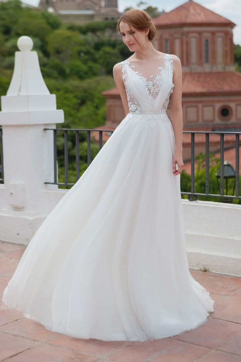 Свадебное платье А-силуэта с выразительным декольте и прозрачной вставкой на спинке.