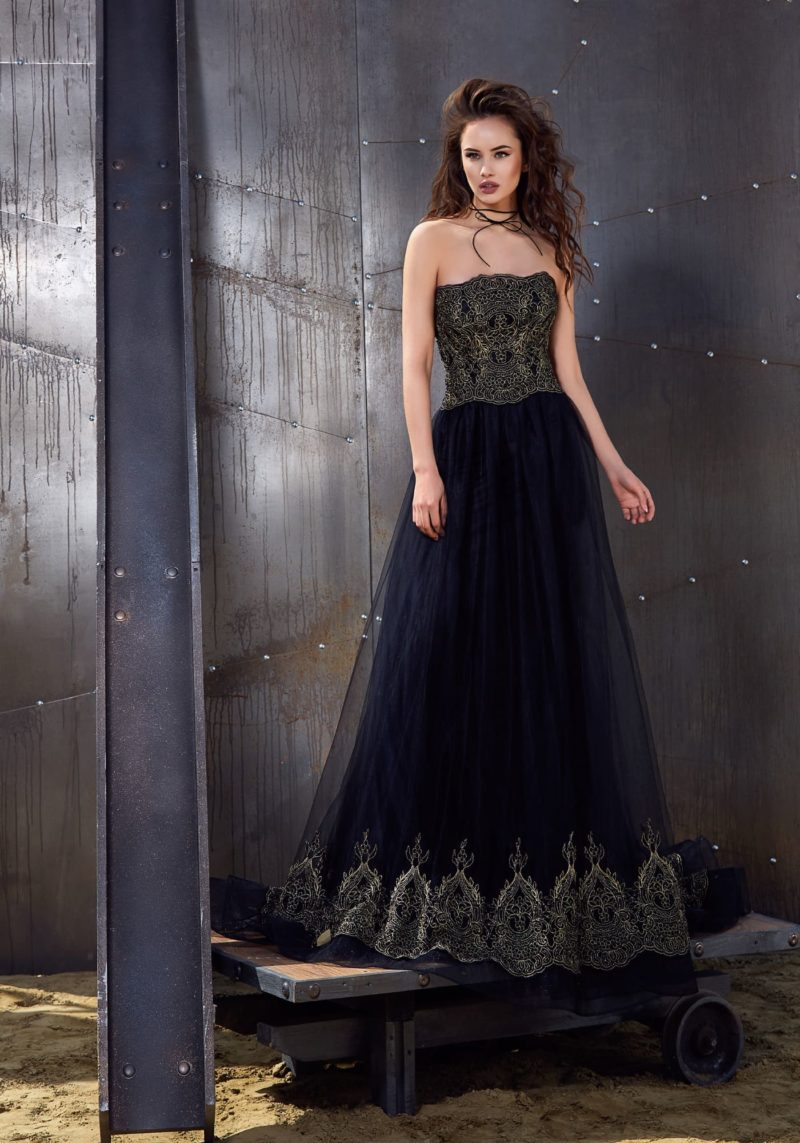 Вечернее платье А-силуэта из черной ткани, украшенное золотистыми кружевом.