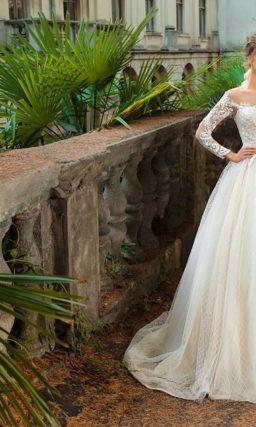 Свадебное платье пышного силуэта с кружевной отделкой, в кремовых тонах.
