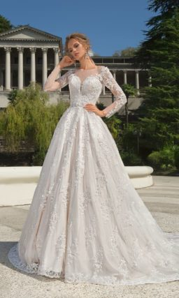 Свадебное платье с великолепной юбкой, закрытым верхом и длинным кружевным рукавом.