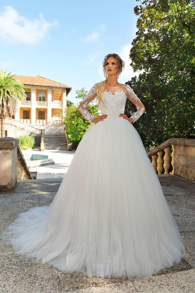 Свадебное платье с элегантным верхом, кружевным декором и многослойной юбкой.