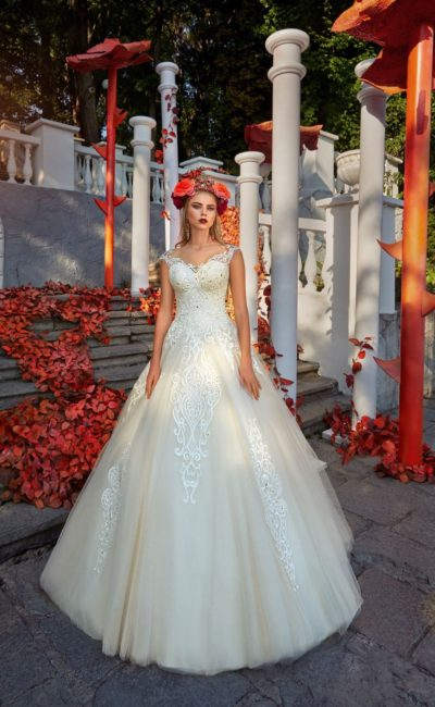 Свадебное платье А-силуэта с кружевным декором и стильной многослойной юбкой.