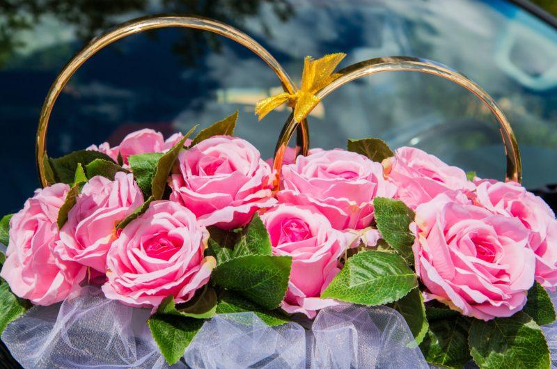 Розовое украшение на машину с крупными бутонами роз и золотыми кольцами.