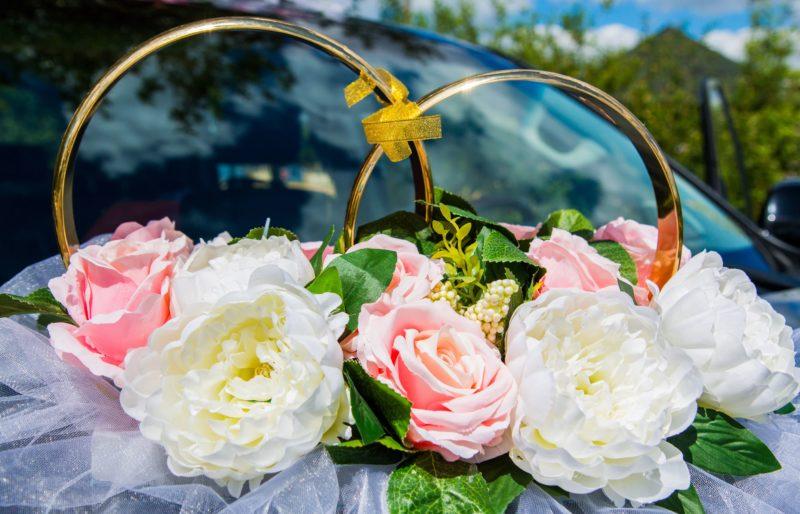 Украшение на машину с крупными белыми и розовыми цветами, а также оборкой.