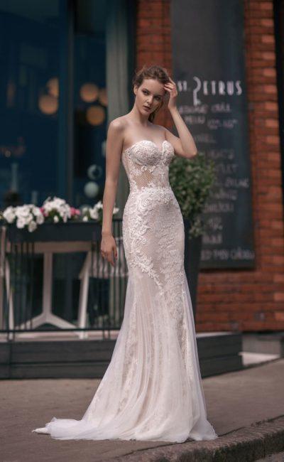 Свадебное платье прямого кроя на бежевой подкладке, украшенное кружевом.