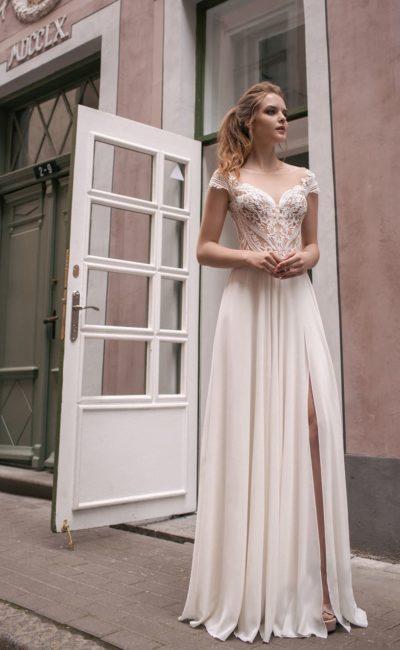 Свадебное платье прямого кроя с полупрозрачным верхом и разрезами на юбке.