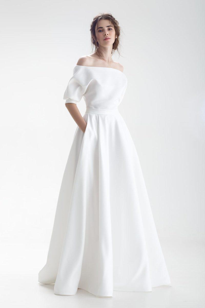 Стильное свадебное платье с портретным вырезом и скрытыми карманами.