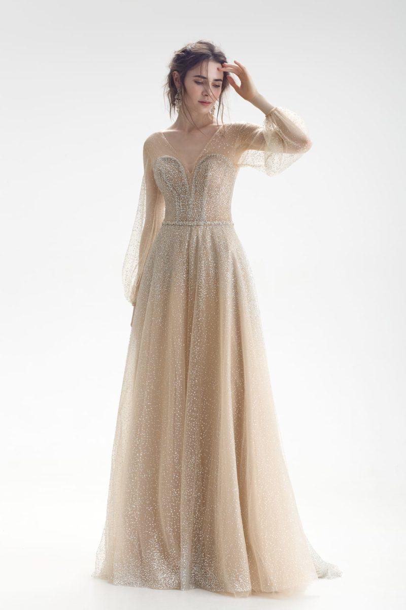 Свадебное платье бежевого цвета, с длинным рукавом и сверкающей отделкой.
