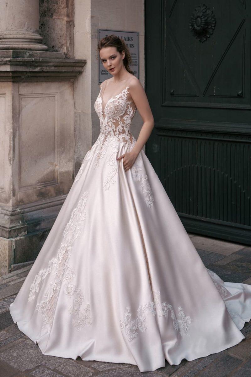 Свадебное платье с атласной юбкой А-силуэта и выразительным кружевным декором.