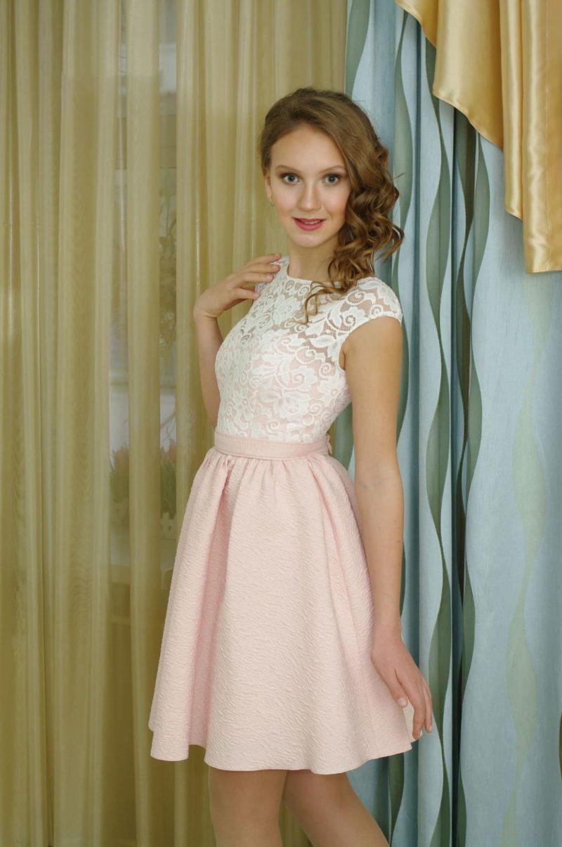 Вечернее платье с розовой юбкой длиной до колена и белым кружевом на лифе.