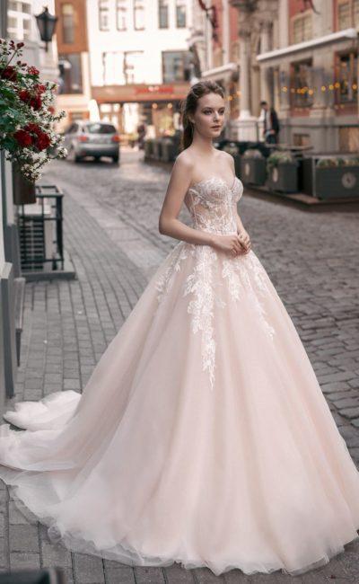 Пудровое свадебное платье с открытым лифом и многослойным подолом со шлейфом.