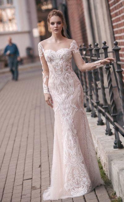 Бежевое свадебное платье облегающего кроя с длинным рукавом и открытой спиной.