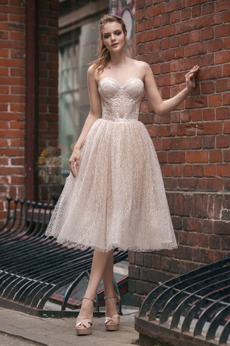 Бежевое свадебное платье с юбкой длины миди и открытым корсетом.