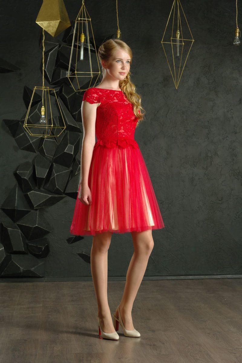 Красное вечернее платье с юбкой до колена и коротким кружевным рукавом.