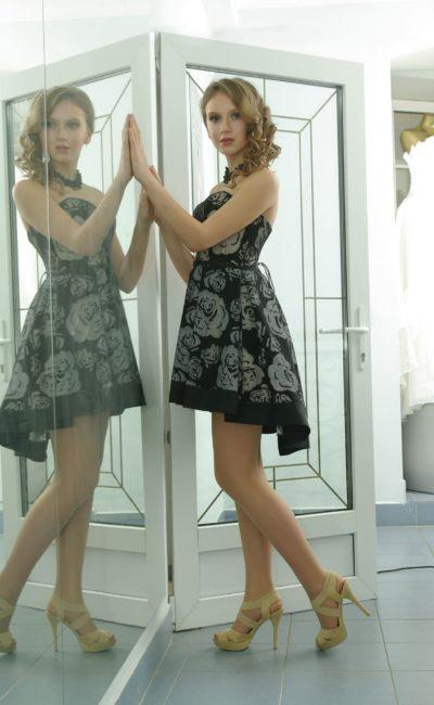 Вечернее платье с выразительной отделкой, открытым лифом и короткой юбкой.
