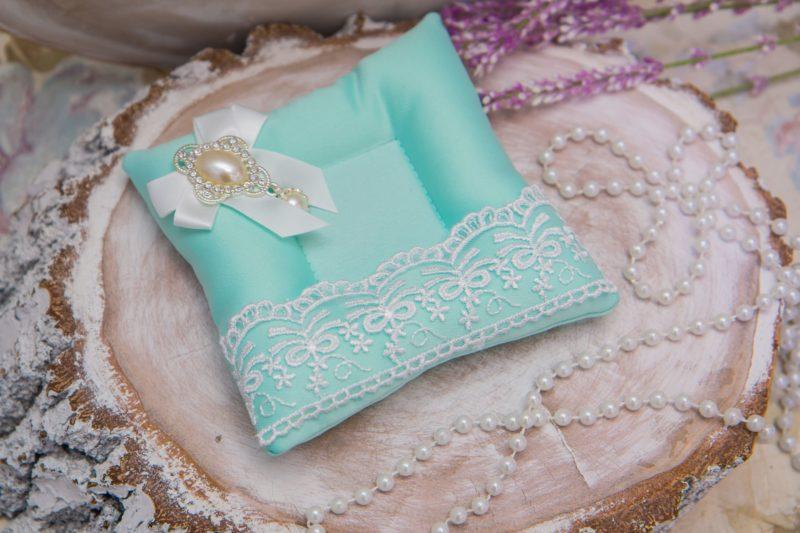 Бирюзовая подушечка для колец, украшенная кружевом и небольшим бантом.