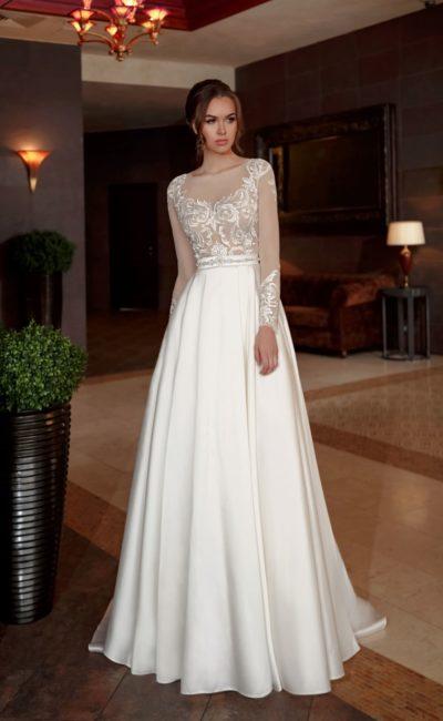 Элегантное свадебное платье с атласной юбкой и полупрозрачным длинным рукавом.