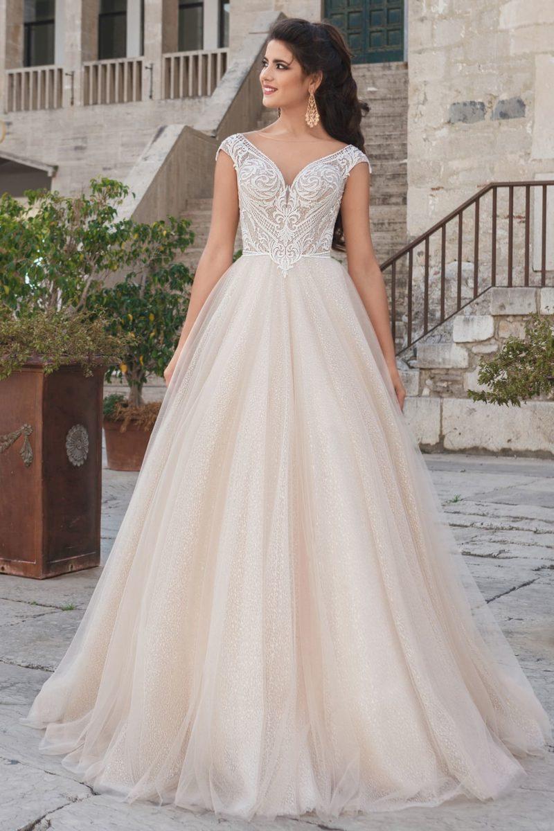 Свадебное платье оттенка слоновой кости с пышной юбкой и коротким рукавом.