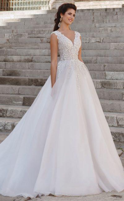 Свадебное платье с элегантным верхом и роскошной пышной юбкой со шлейфом.