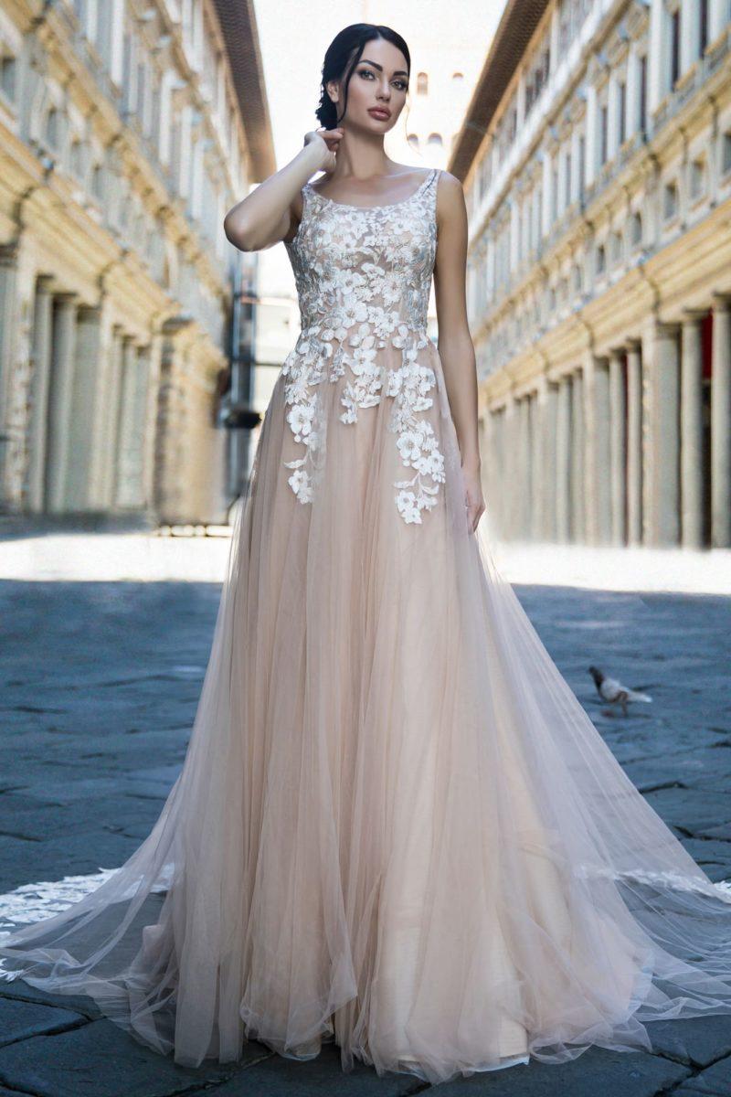 Свадебное платье бежевого цвета с белым кружевным декором и шлейфом.