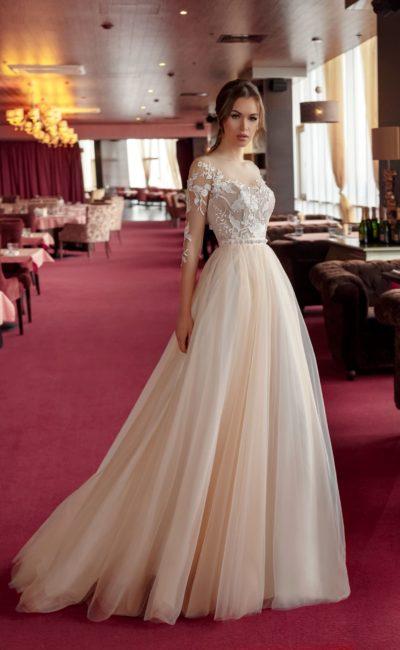 Бежевое свадебное платье с белой кружевной отделкой верха с прозрачным рукавом.