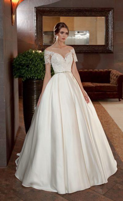 Атласное свадебное платье с пышной юбкой, декорированное по верху кружевом.