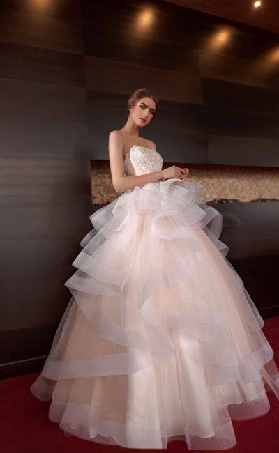 Персиковое свадебное платье с многоярусной юбкой и стильным открытым корсетом.