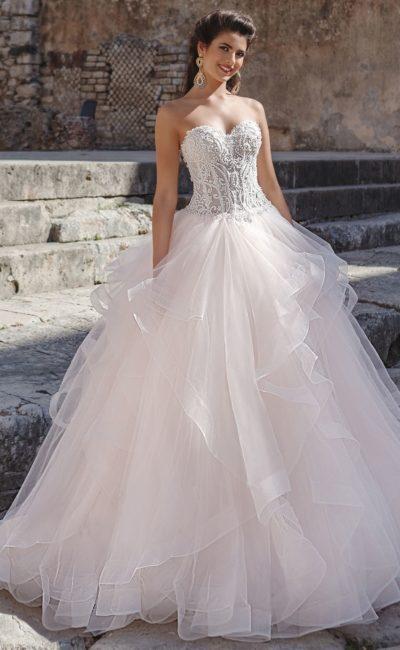 Свадебное платье пышного кроя с открытым лифом и многоярусной юбкой.