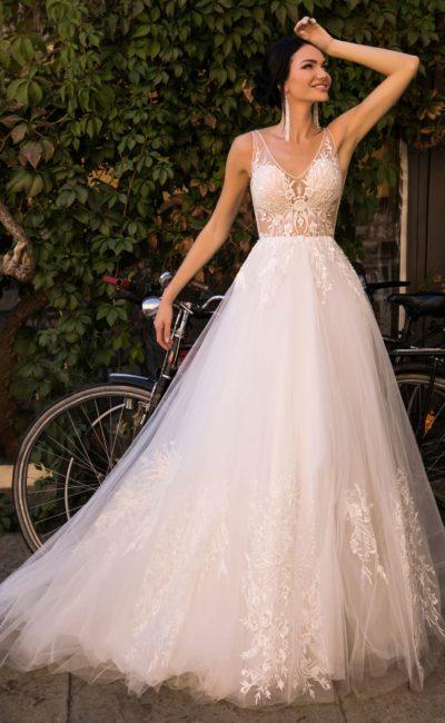 Пышное свадебное платье с полупрозрачным верхом и небольшим шлейфом.