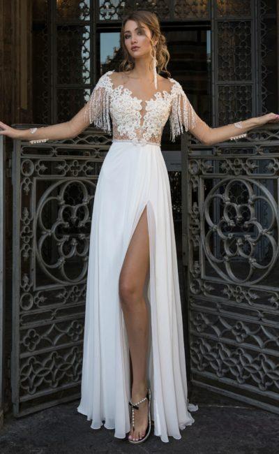 Прямое свадебное платье с полупрозрачным верхом и рукавами из бахромы.