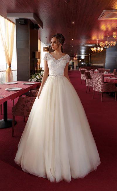 Пышное свадебное платье с подчеркнутой талией и короткими кружевными рукавами.