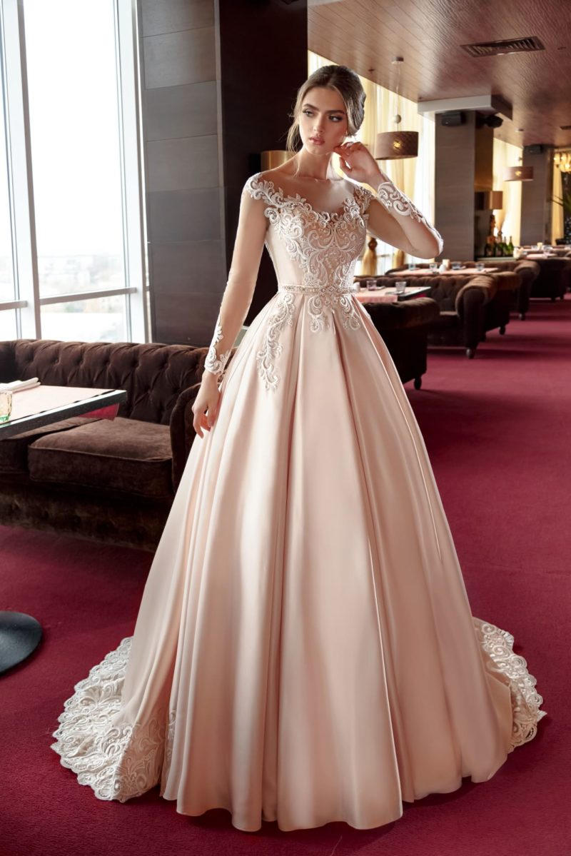 Атласное свадебное платье кремового оттенка с элегантной отделкой верха.