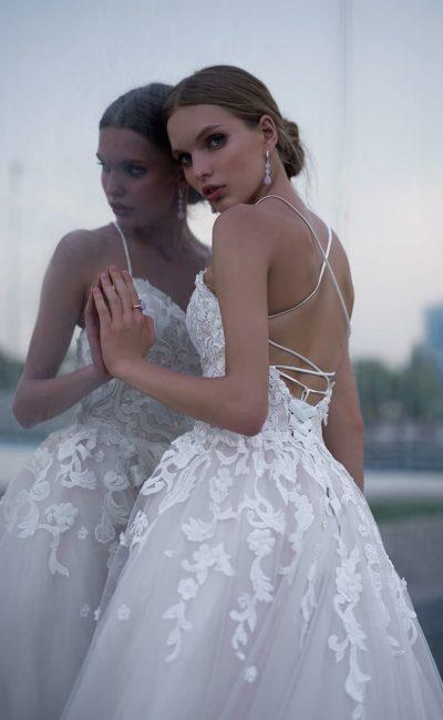 Пышное свадебное платье с многослойной юбкой и открытой спинкой.