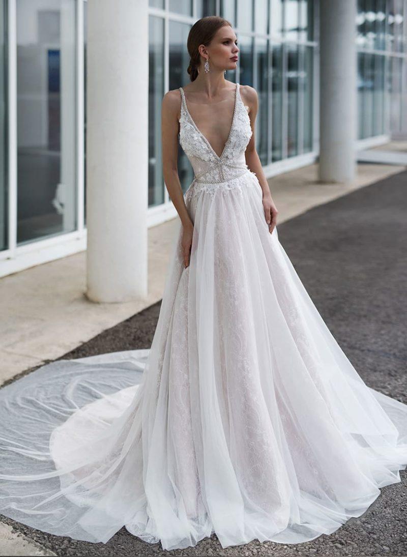 Стильное свадебное платье женственного кроя с глубоким декольте.