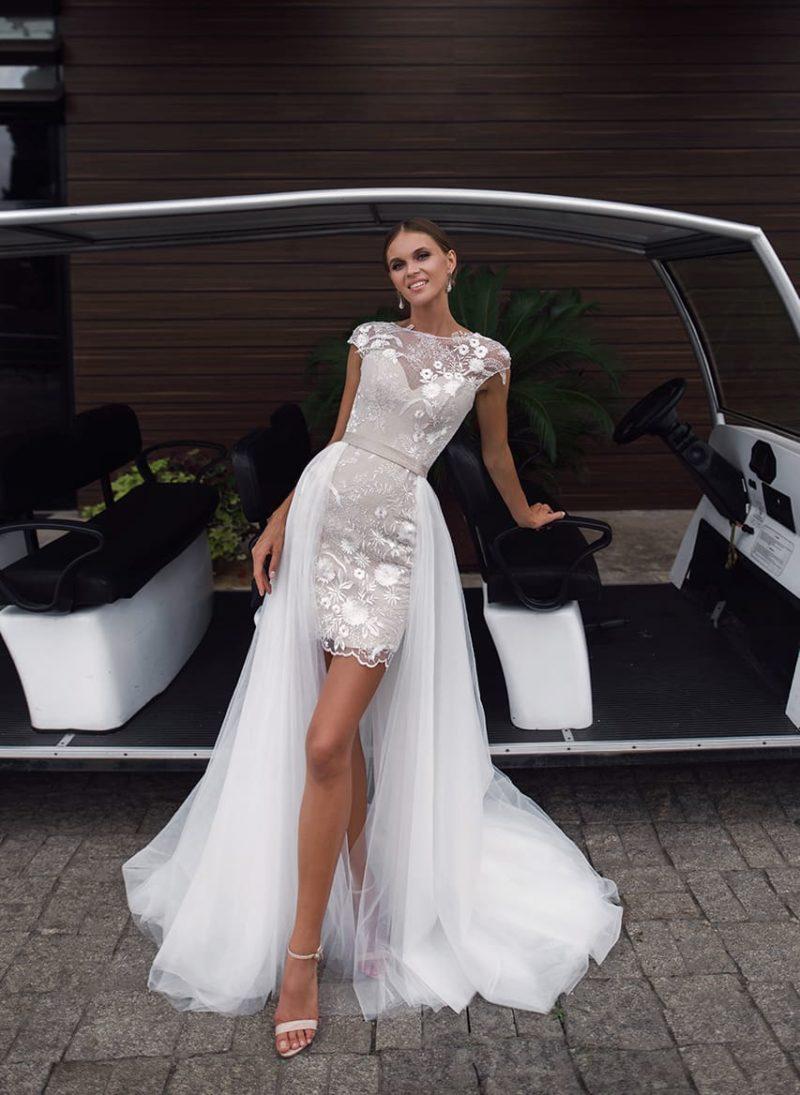 Короткое свадебное платье бежевого цвета с длинным белым шлейфом.