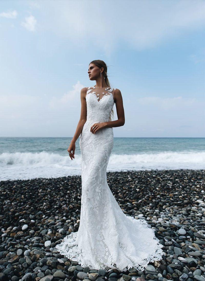 Облегающее свадебное платье с длинным шлейфом и декором из кружева.