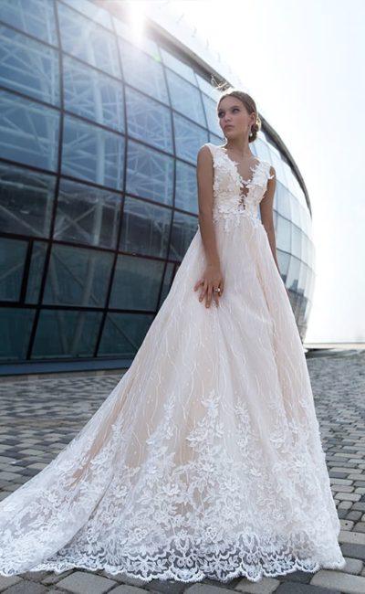 Бежевое свадебное платье с кружевной отделкой и многослойным подолом.