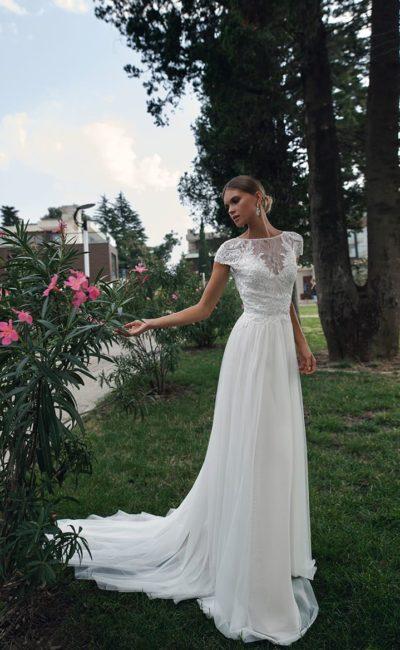 Элегантное свадебное платье прямого кроя с вырезом под горло и рукавом.