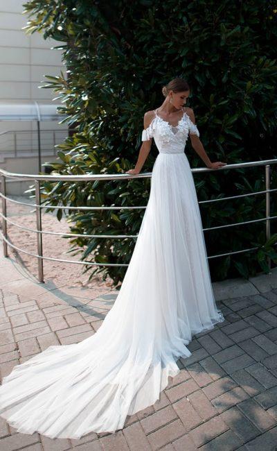 Романтичное свадебное платье с бретелями на предплечьях и длинным шлейфом.
