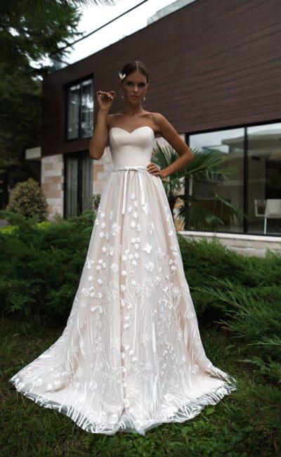 Розовое свадебное платье с открытым лифом и цветочным декором по подолу.