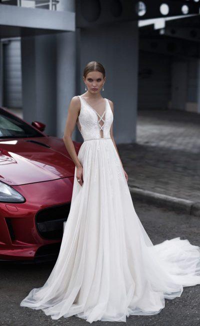 Женственное свадебное платье с эффектным декольте и длинным шлейфом.