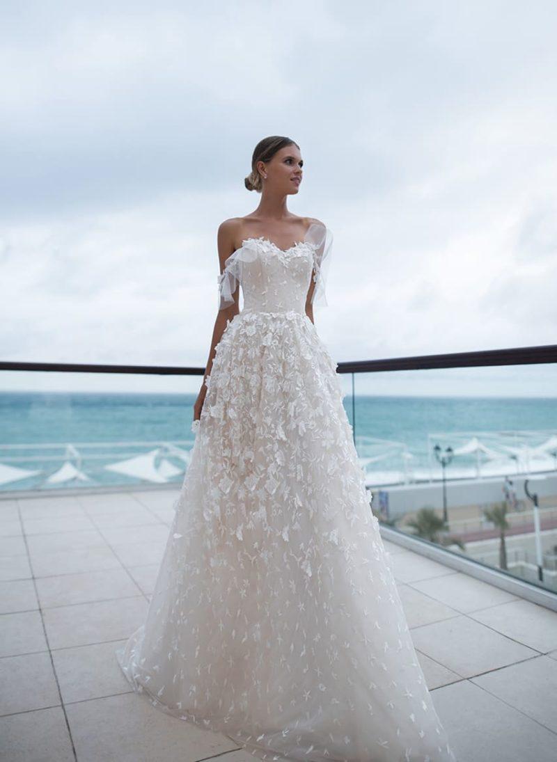 Открытое свадебное платье пудрового оттенка с объемным декором подола.